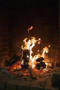 Blazing fire by brick.