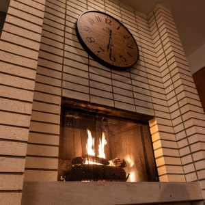 Clock above a fireplace.