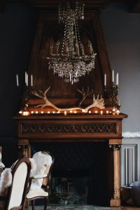 Fireplace by chandelier.