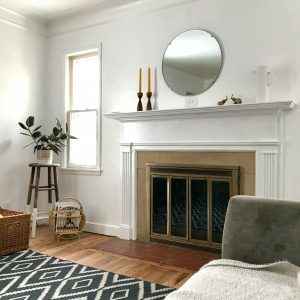 White room with covered fireplace.
